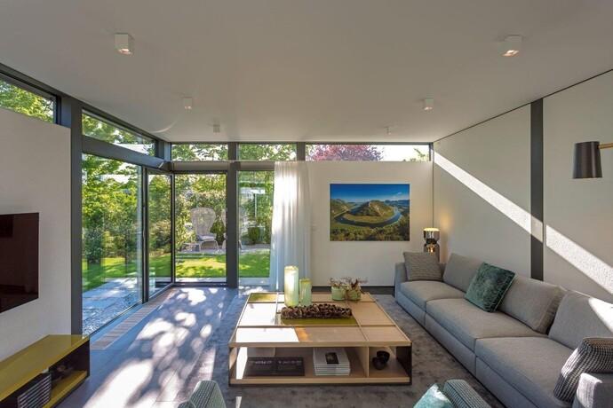 """Die großen Fensterflächen verschmelzen den Wohnbereich mit der Außenlandschaft. Doch auch die Technik im Haus ist """"grün""""."""