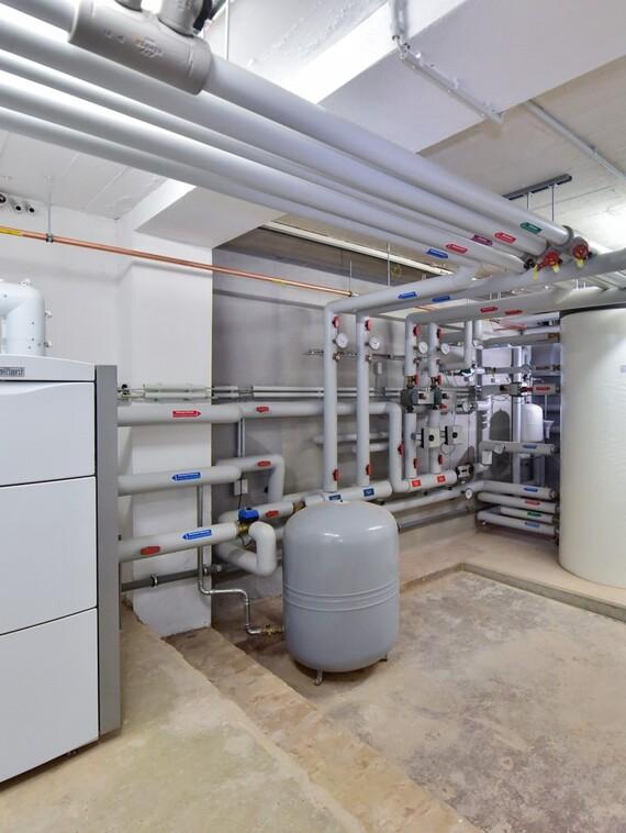 Übersichtlich: Das bodenstehende Gas-Brennwertgerät mit 65 KW modulierender Leistung plus die thermische Solaranlage versorgen die neue Wohnanlage; rechts der Multi-Funktionsspeicher mit 1.000 Liter Inhalt.