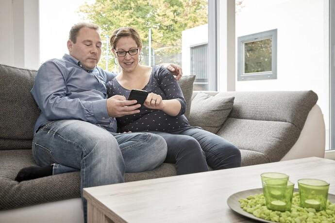 """Bequemer geht es kaum: Per Fingerwisch auf dem Smartphone können die jungen Bauherrn vom Sofa aus die Wunschtemperatur beeinflussen oder """"mal eben"""" checken, wie viel Sonnenenergie sie an diesem Tag schon geerntet haben."""