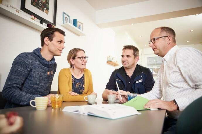 """Familie Kaiser (v. li., hier mit Fachhandwerker Freissler und Vaillant-Fachberater Andreas Hoberg) ist begeistert: """"Wir wollten keine Fenster wie Schießscharten – und haben deswegen in eine ökologische Heizung und nicht nur in Dämmung investiert."""""""